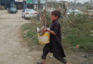 離れた共同水栓まで水を汲みに行く住民たち